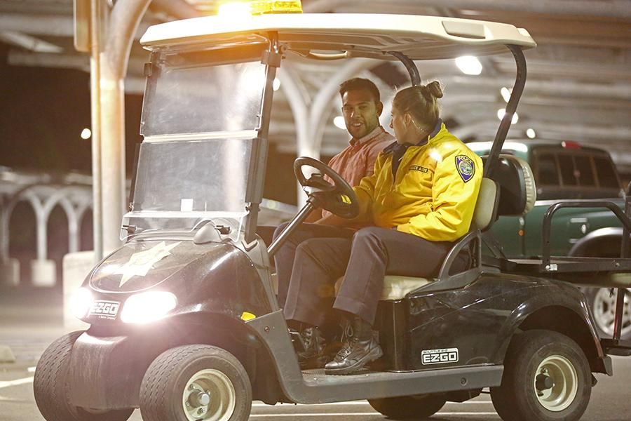 Police aide Ashley Crandell, an administration of justice major, and Evelio Perez, an engineering major, take a ride in Lot 10 on May 2.