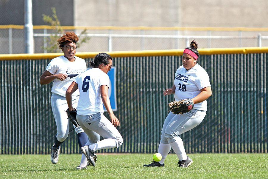 Comet center fielder Julian Robinson (far left), left fielder Regina Balan (center) and right fielder Catherine Nieve-Duran try to hastily pick up the ball during CCC's doubleheader loss to Napa Valley College  on April 26.