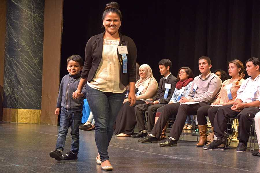 Karla Juarez walks across the stage accompanied by her son during the 57th Annual Scholarship Award Ceremony, hosted by the College Foundation Board, where recipients of scholarships and awards were honored in the Knox Center on May 4.
