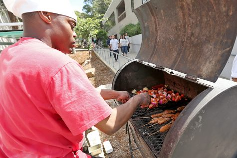 Culinary arts major Carlos Garrison tends to salmon kebabs during the United Faculty Barbecue event near the chess tables in front of the Applied Arts Building on Wednesday. The event featured entertainment as well as free lunches for students.