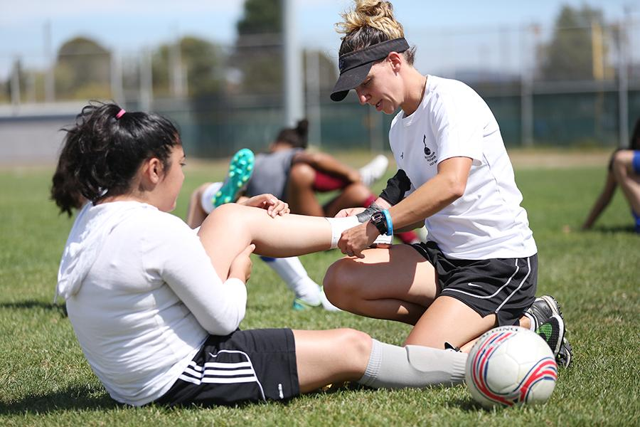 Women's soccer coach Brittany Castillo helps Christy Garcia remove tape from her ankle during soccer practice at the Soccer Field on Monday.