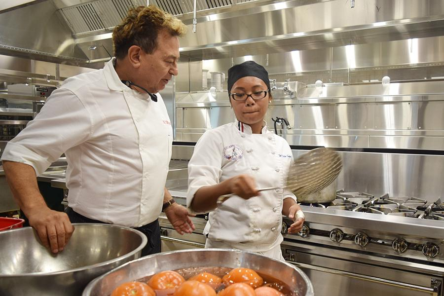 Culinary arts Chairperson Nader Sharkes and student Kyle DeLos Santos submerge hot tomatoes under cool water in the Student and Administration Building on Friday.