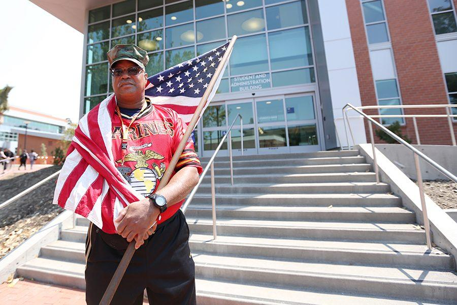 Leon Watkins wraps himself in the American flag in front of the Student and Administration Building on Monday. Watkins has worked in the Veterans Corner for the past seven months assisting veterans with their educational benefits and needs.