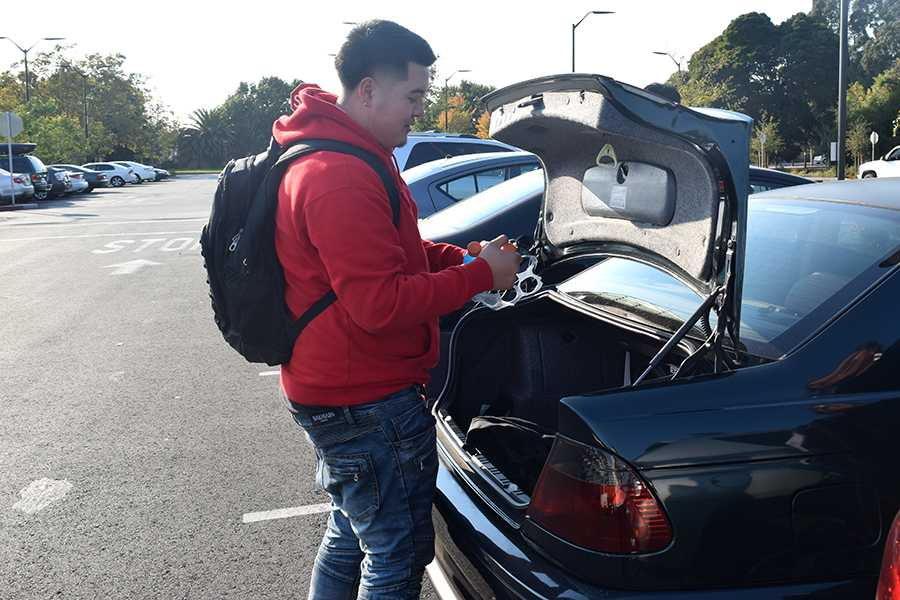 Business major JayJay Douangpinya pulls out a beverage from his trunk before heading to class in Contra Costa College's Parking Lot 3  on Monday.