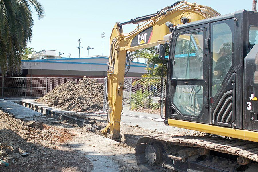 A construction worker with Kleinfelder, Inc. digs out dirt inside a 15-foot trench in Lot 6 in front of the Gymnasium on Aug. 16.