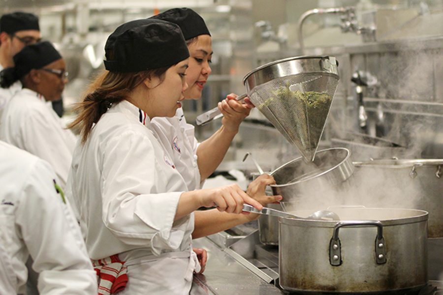 Culinary+arts+students+Kate+Bautista+%28left%29+and+Genalyn+Sabrinano+prepare+pasta+for+the+Taste+of+Italy+Iron+Chef+competition+in+the+Aqua+Terra+Grill+on+Thursday.