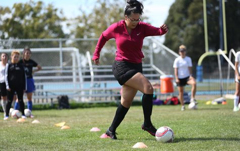 Administration of justice major Ingrid Gonzalez dribbles through cones during soccer practice at the Soccer Field on Monday.