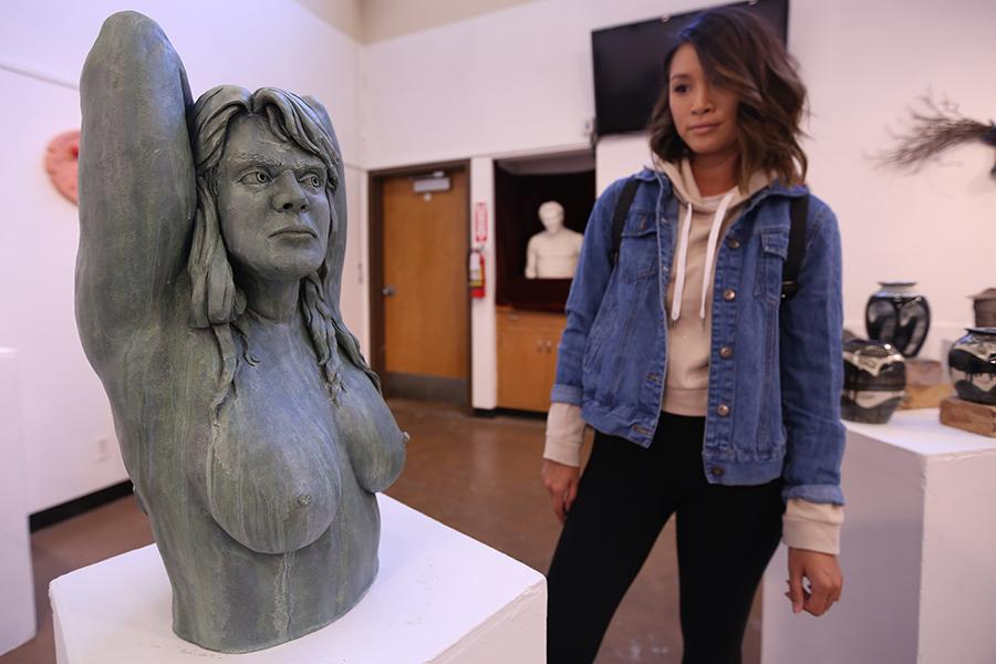 Health and human services major Carolyn Tran surveys a sculpture by CCC alumnus C.E. Small in the Eddie Rhodes Gallery on Thursday.