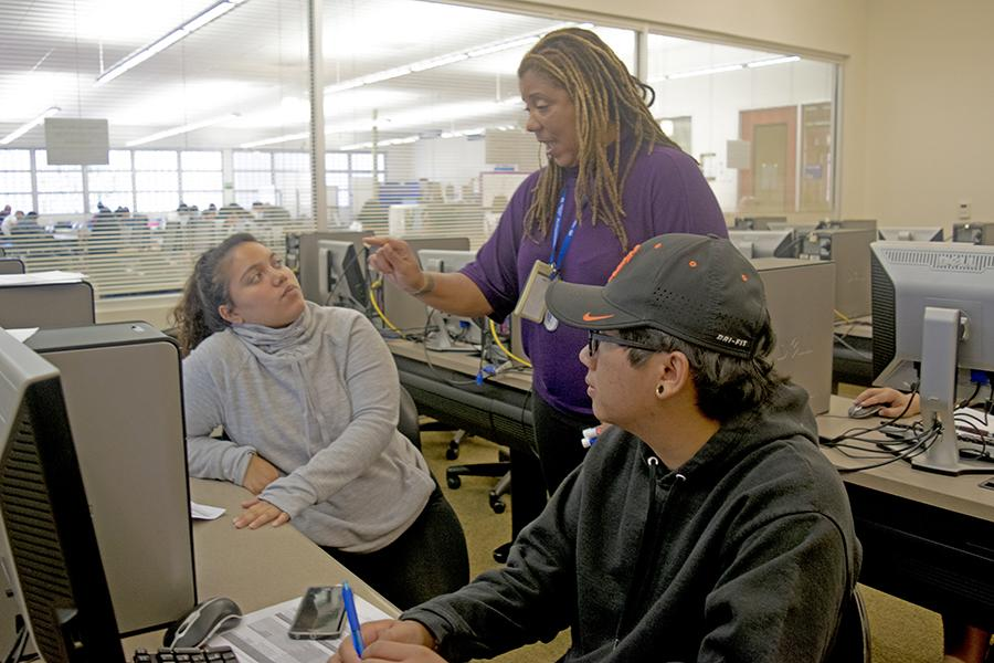 Transfer Coordinator Andrea Phillips (center) helps two students access the Transfer Admission Planner website during the Transfer Admission Guaranteed workshop in the Library on Aug. 29.