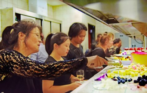 Dance major Wendy Huang (left) grabs some cheese during Chocolate and Champagne event hosted by the culinary arts department in the Aqua Terra Grill on Oct. 8. The event is used to fund raise for students going to Italy.