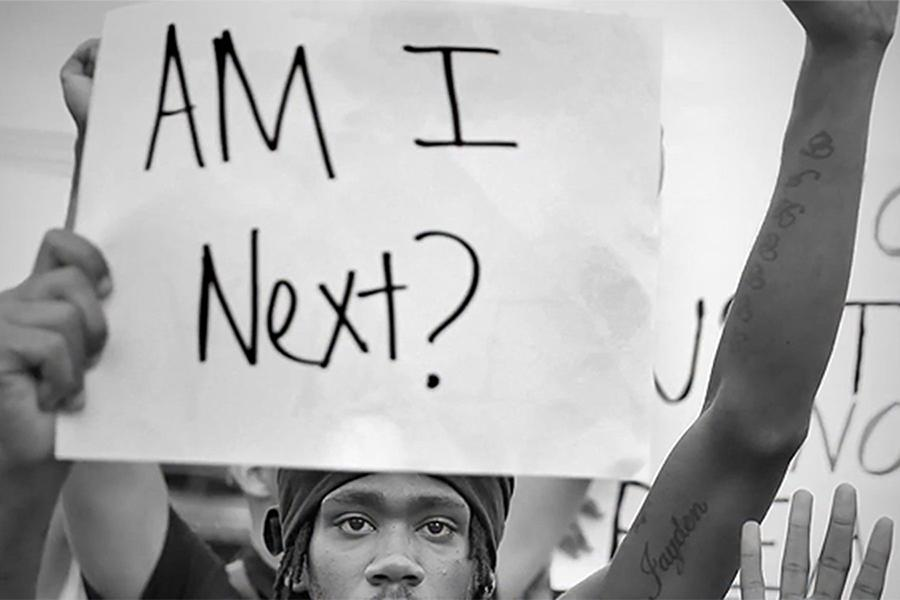 """In a photograph from the film """"13th,"""" a protester holds up a sign stating, """"Am I Next?"""" referring to the possibility of his death at the hands of police. """"13th,"""" directed by Ava DuVernay, explores the historical oppression of black communities and the mass incarceration of African-Americans starting from the end of slavery in 1863 to the present day police brutality epidemic."""
