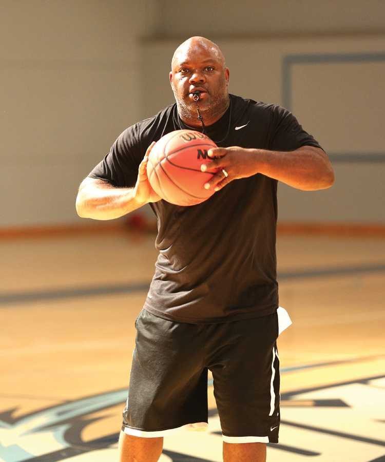 Women's basketball coach Vince Shaw passes the ball to a player during a practice drill in the Gymnasium on Thursday.