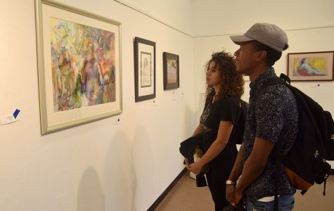 "Business major Clarence Bonilla (right) and undecided major Christina Hantakas observe pieces of art in the Eddie Rhodes Gallery as part of the ""Ageless Expression"" exhibit in A-5 on Oct. 11."