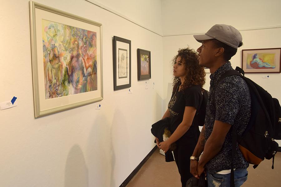 """Business major Clarence Bonilla (right) and undecided major Christina Hantakas observe pieces of art in the Eddie Rhodes Gallery as part of the """"Ageless Expression"""" exhibit in A-5 on Oct. 11."""