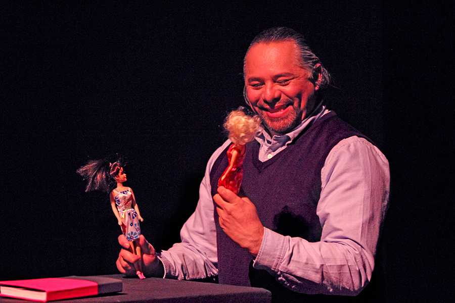 """Drama department Chairperson Carlos-Manuel Chavarría plays with two dolls during a scene of the one person play, """"Joto!: Confessions of a Mexican Outcast,"""" in Knox Center on Friday."""