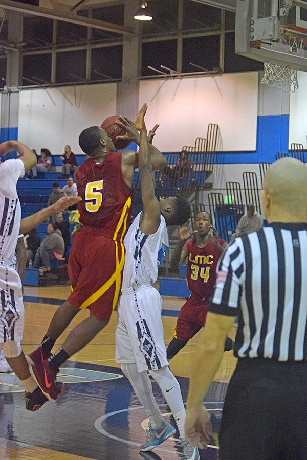Comet guard Damar Dunn attempts to draw a charge as Los Medanos College guard Mark Thomas drives for a layup during CCC's 74-71 loss in the Gymnasium on Jan. 27.