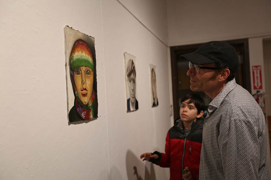 "Forestville resident Michael Baker and his son examine a piece of art during the opening of the ""Prosopagnosia: Do I Know You?"" reception at the Eddie Rhodes Gallery in the Art Building on Friday"