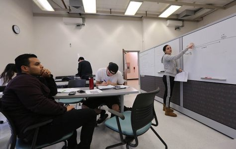 Biology major Oscar Castillo (left) listens to biology major Maria Rodriguez (right) explain a problem using the new whiteboard and equipment in PS-109 in the Physical Science Building on Monday.