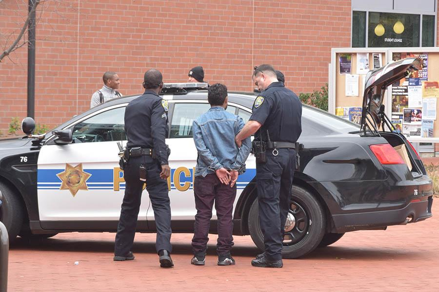Police Services Lt. Tom Holt (right) and Corporal Charles Hankins arrest a Contra Costa College student detained for possession of marijuana in the Campus Center Plaza on Feb. 15.