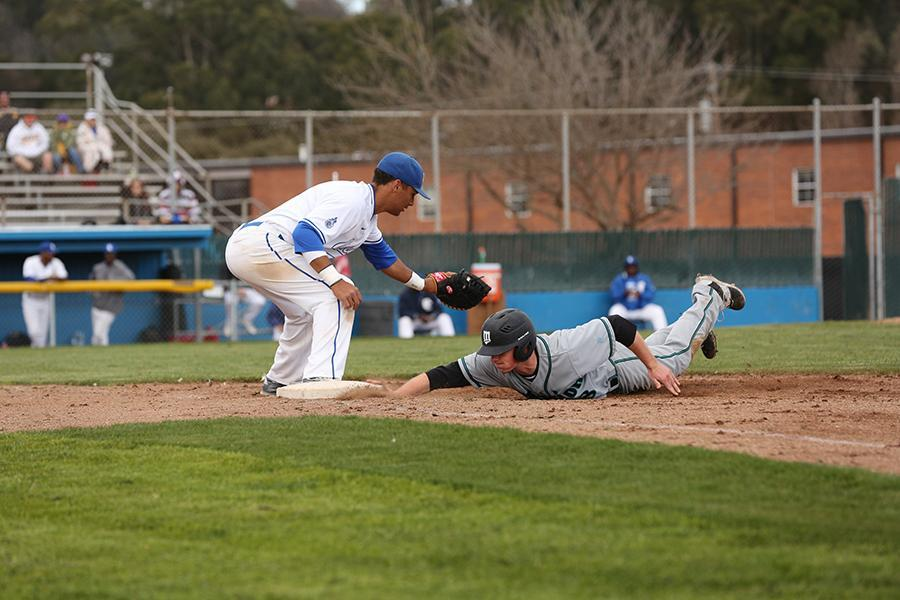 Saint outfielder Tyler Barry slide back into first before the tag by Comet first baseman Eric Whitfield during CCC's 6-2 loss to Mission College at the Baseball Field on Sunday.