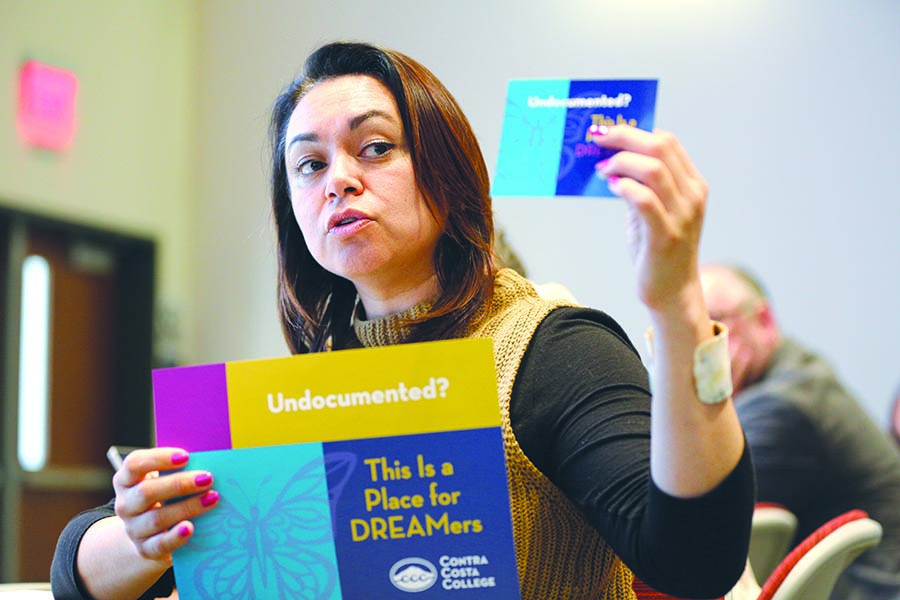HSI STEM Manager Mayra Padilla holds up signs in support of undocumented students during the College Council Meeting in GE-225 on Thursday.