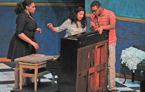 "Piano tuner Victor Manuel (right) played by Sean Teal, flashes a light into a piano as Sofia Celia, played by Jelaine Maestas, and Maria Celia, played by Akilah Kamau, watch during a performance of ""Two Sisters and a Piano"" in the Knox Center on Thursday.Piano tuner Victor Manuel (right) played by Sean Teal, flashes a light into a piano as Sofia Celia, played by Jelaine Maestas, and Maria Celia, played by Akilah Kamau, watch during a performance of ""Two Sisters and a Piano"" in the Knox Center on Thursday."