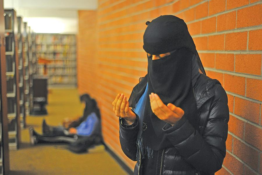 Muslim student prays in the behind the book- shelves in the Library on March 20. The Muslim Student Association is coordinating efforts to create a designated space for praying.