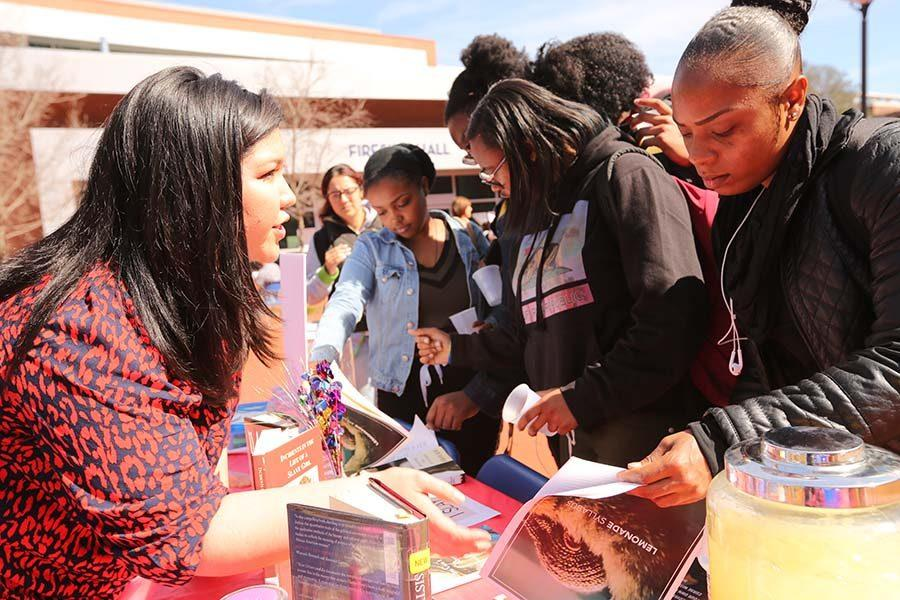cody casares / The Advocate HSI STEM Coordinator Kelly Ramos (left) explains a course syllabus to political science major Antonia Phillips (right) during the International Women's Day event in the Campus Center Plaza on March 8.