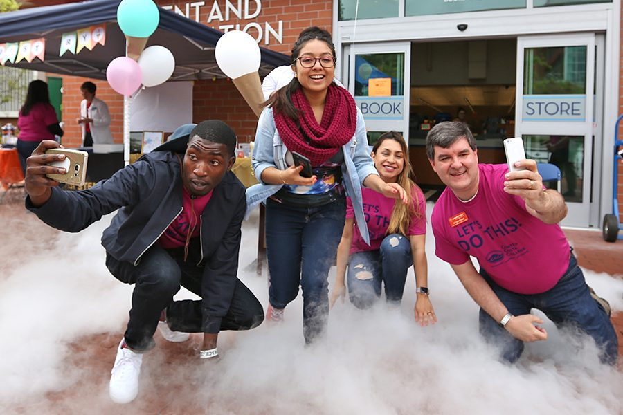 Student Life Coordinator Joel Nickelson-Shanks (left) takes a selfie above liquid nitrogen smoke with biology major Abigail Serrano (center left), biological major Katherin Guevara (center right) and SparkPoint Coordinator Bill Bankhead during the Super Saturday event in the Student Center Plaza. on Saturday.