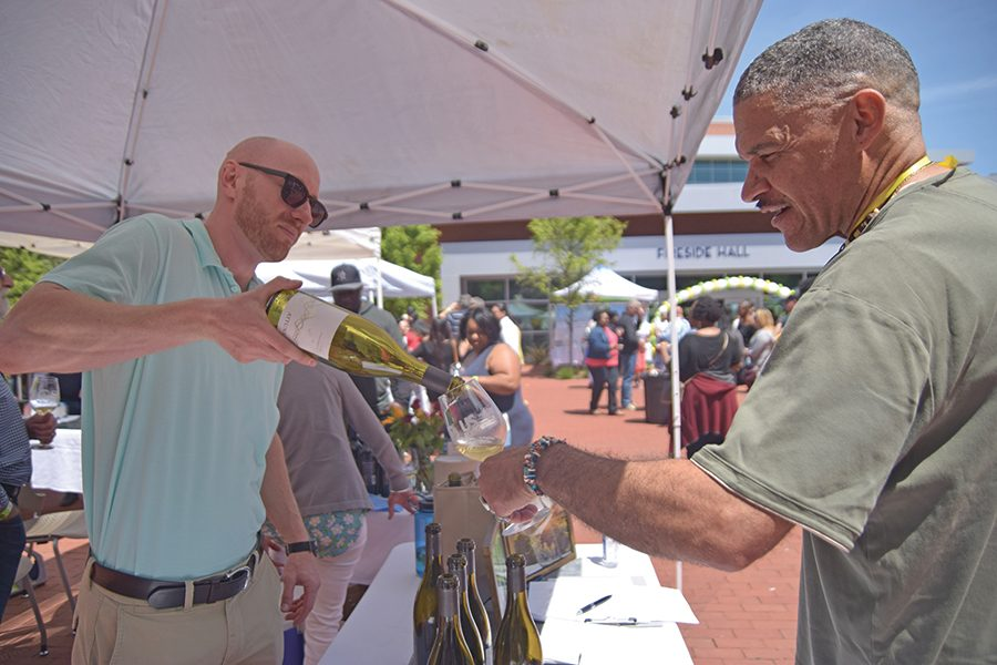Attune Wine representative Jason Campbell (left) pours Richmond resident Barry Grant a glass of 2015 chardonnay during the Food and Wine Event in the Campus Center Plaza on Sunday.