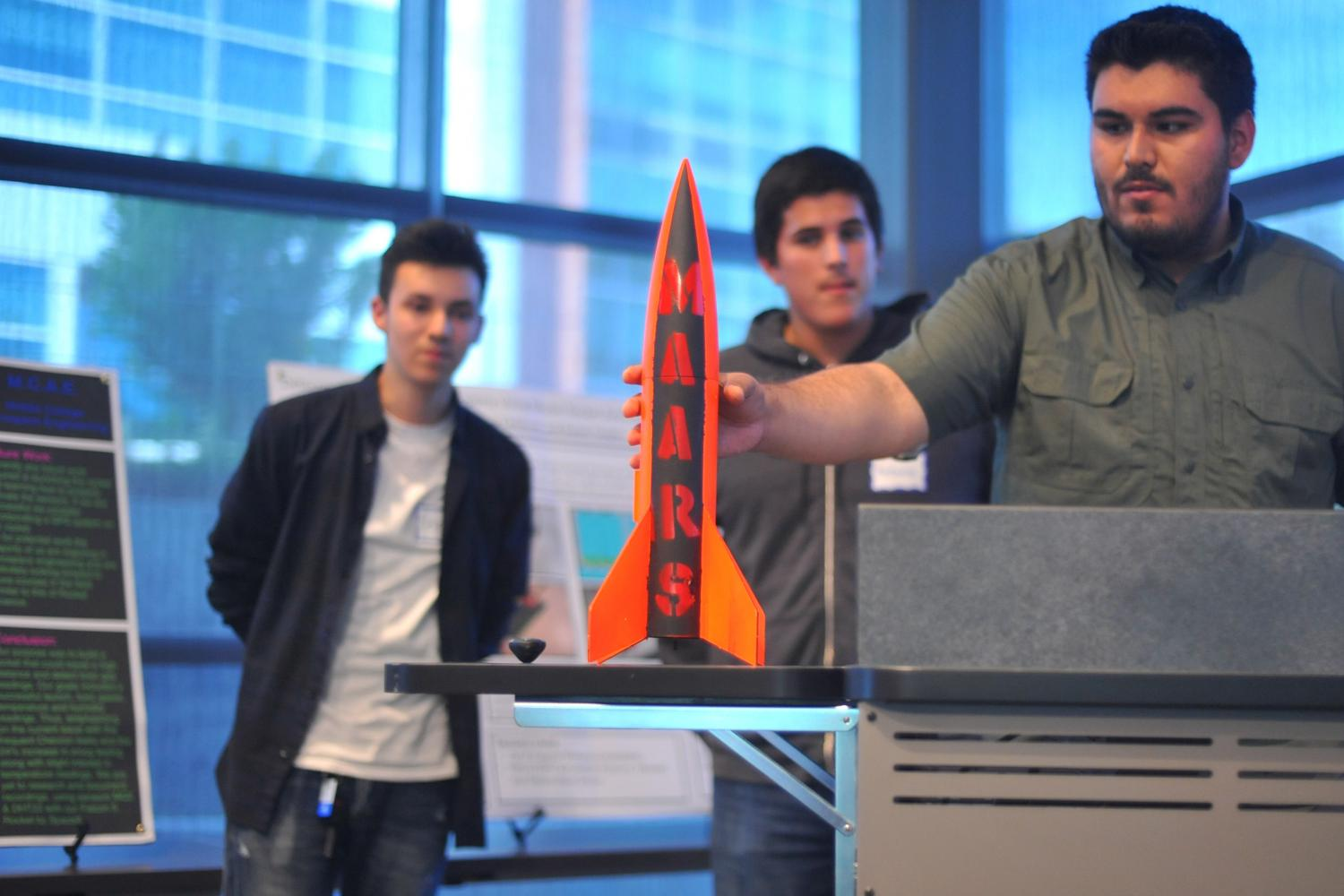 Engineering major Manuel Ayala (right) presents a rocket his team worked on during the semester during the inaugural Student Research Symposium event held in Fireside Hall on May 4.