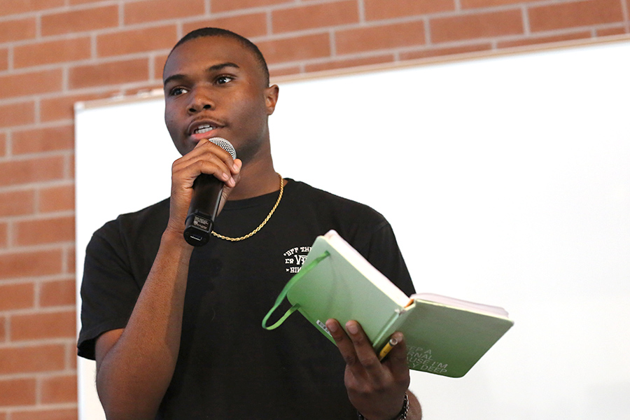 Student+life+ambassador+Nijzel+Dotson+recites+a+poem+he+wrote+to+the+crowd+during+the+%22Poetry+Night%22+event+in+Fireside+Hall+on+Monday.