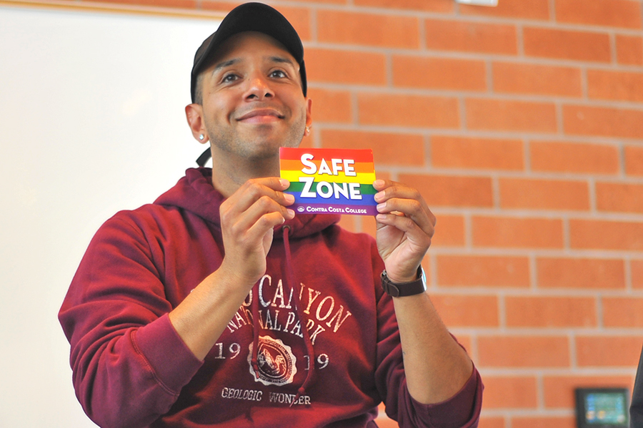 Psychology major Enrique Duarte holds a safe zone card during the Alphabe+'s Club
