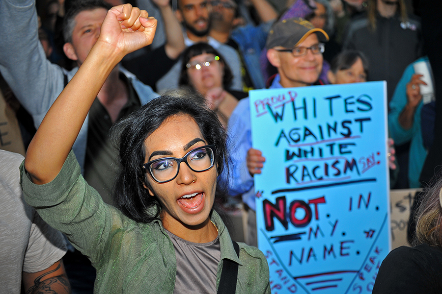 A+protester+raises+her+fist+with+the+crowd+as+they+chant+and+start+marching+during+the+Defend+Charlottesville+rally+in+downtown+Oakland%2C+Calif.+on+Aug.+12%2C+2017.
