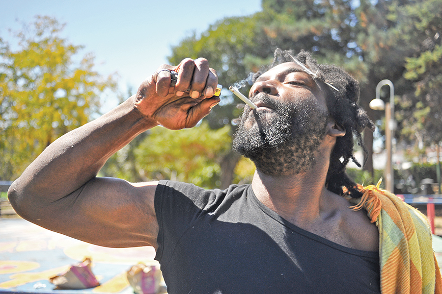 Berkeley resident Alen Malik smokes a pre-rolled joint of OG Kush shakes cannabis from the Munchie Movement in People's Park in Berkeley on Aug 25.