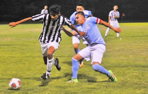 Evergreen Valley College center Edson Mendoza dribbles past Comet captain Juvenal Pena during a home soccer game on the Soccer Field Friday.