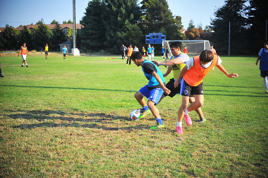 A player dribbles past two defenders during a possession drill during the men's soccer practice on Aug. 17 on the Soccer Field.