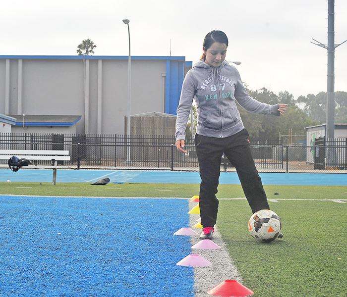 Business major Juana Ortiz dribbles the ball through cones during a ball touching drill at the women's soccer team practice on the Football Field on Tuesday.