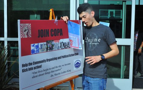 Club member Ricky Cusguen adjusts a Community Organizing and Political Action Club (COPA) sign outside Fireside Hall during a COPA event on Monday.