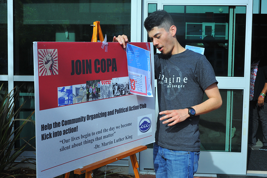 Club+member+Ricky+Cusguen+adjusts+a+Community+Organizing+and+Political+Action+Club+%28COPA%29+sign+outside+Fireside+Hall+during+a+COPA+event+on+Monday.