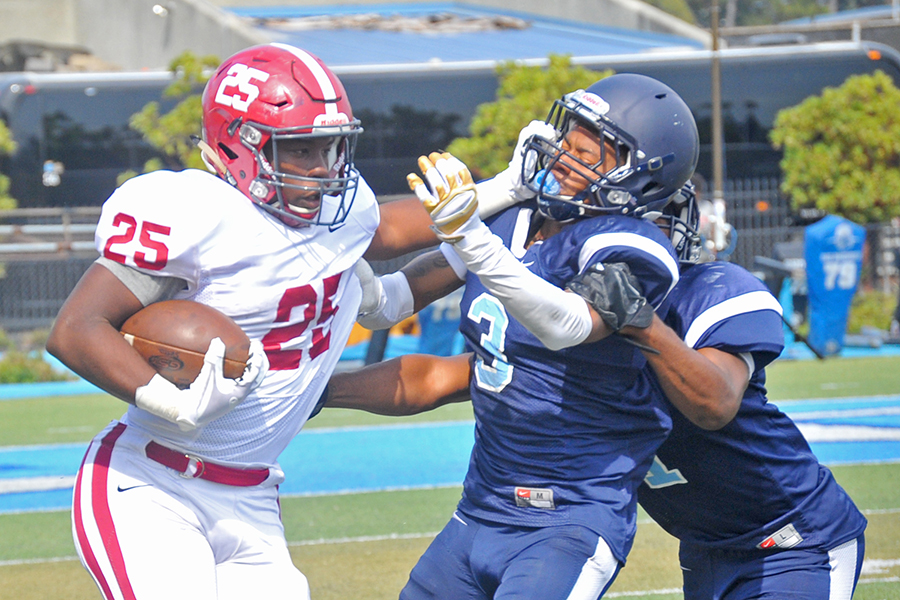 Wolverine running back Dalton Gee pushes off Comet defensive linemen Marcus Pippen and Dayvonne (Bubba) Greenwood during Contra Costa College's 56-28 defeat to Sierra College at Comet Stadium on Saturday.