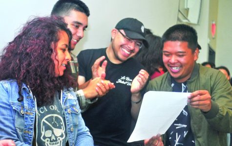 Gabriel Sanchez (middle right) and nursing major Joey Lumagbas (right) join La Raza Student Union and Puente Club members as they read lyrics for a song written by economics major Oscar Martinez during the Deferred Action for Childhood Arrivals, DACA, Info Night in the GE-225 on Friday.