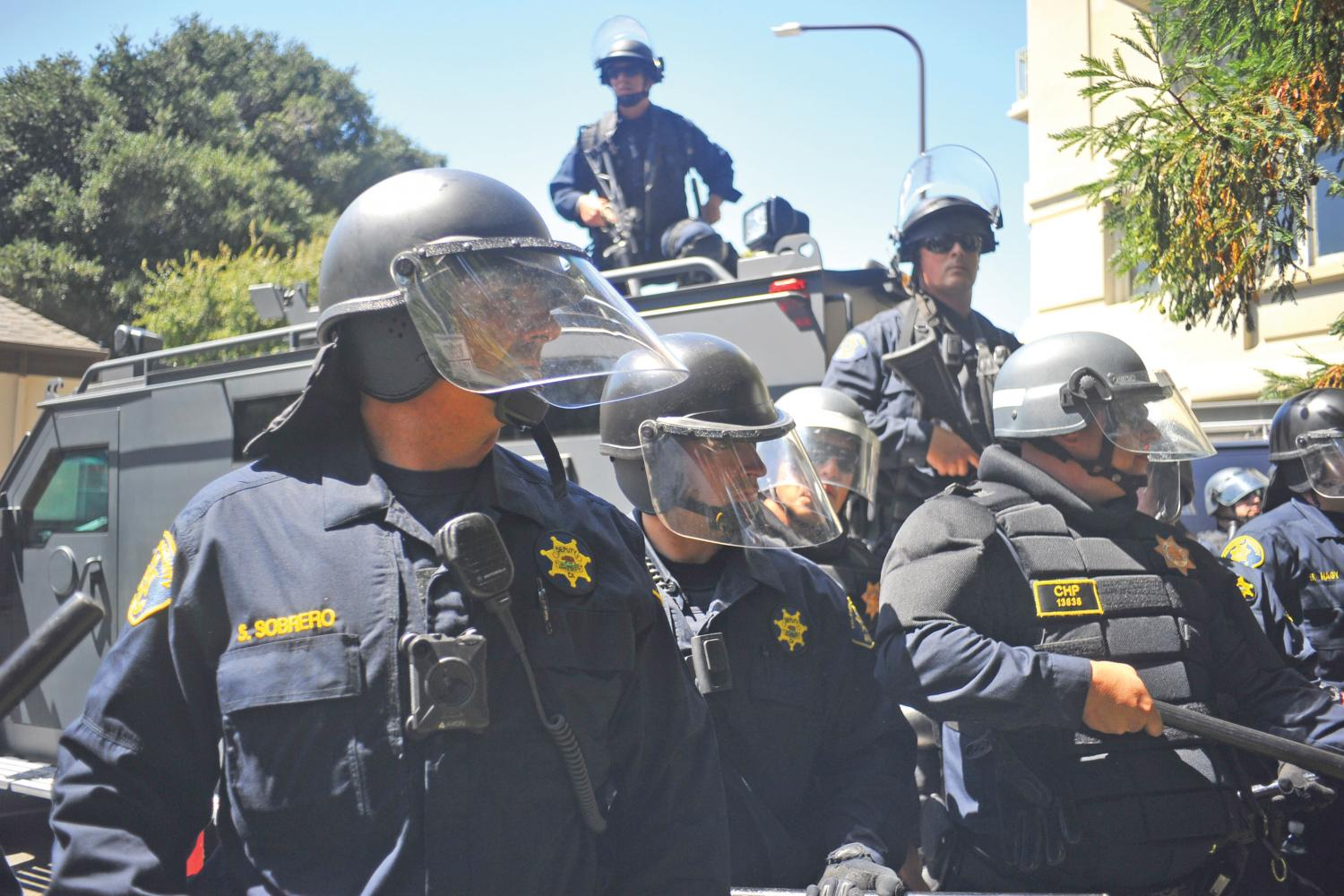 Berkeley police officers form a line in front of a Mine- Resistant Ambush Protected (MRAP) vehi- cle during a protest at Martin Luther King Civic Center Park in Berkeley on Aug. 27. Police depart- ments across the country have begun to militarize their tactical units.