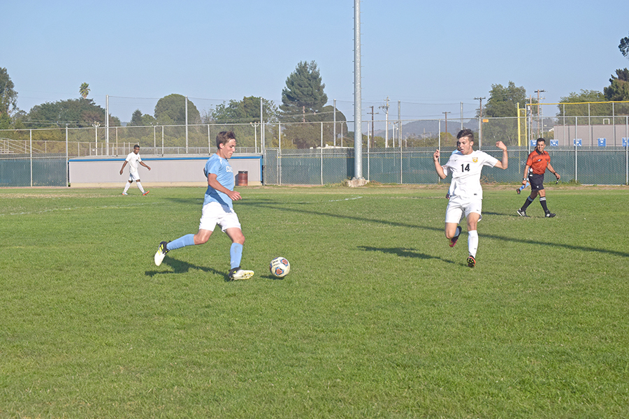 Comet defender Reece Burkhart dribbles the ball as Roadrunner forward Marlon Rowe approaches during Contra Costa College's draw against Butte College in the Soccer Field on Friday, 2-2.
