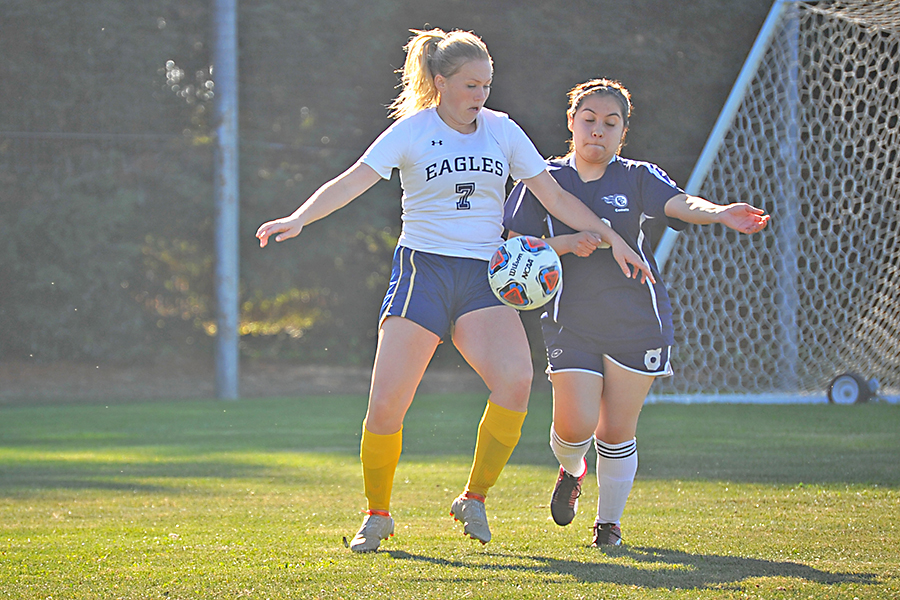 Mendocino College midfielder Emmylee Holt fights a Comet defender for possession of the ball in CCC's season opener at the Soccer Field on Friday.