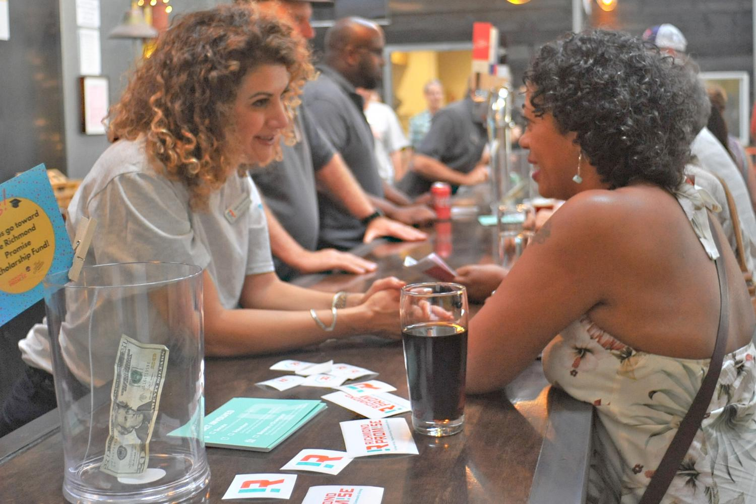 Contra Costa College president Mojdeh Mehdizadeh talks with an East Brother's Beer Company customer during the Cheer for the Promise Fundraising event on Sept. 30 in Point Richmond.