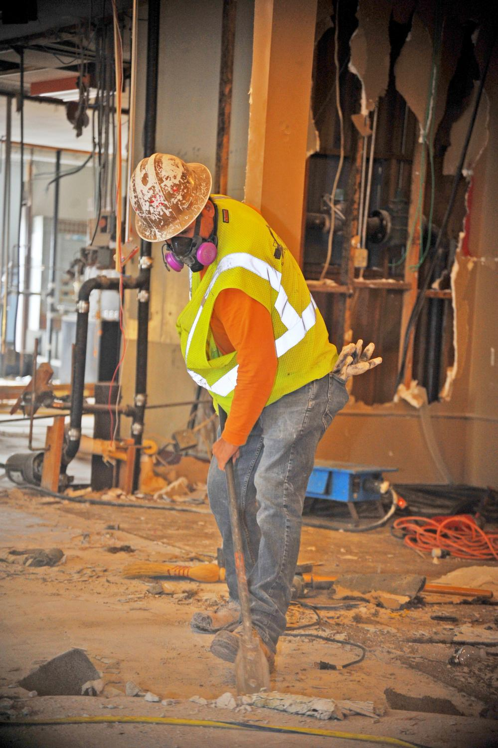 Construction worker Armando Garcia demolishes the floor of what used to be the Three Seasons Restaurant.