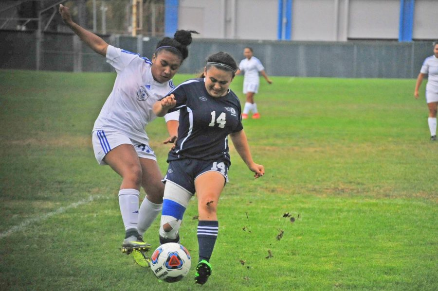 Comet defender  Ashley Portillo (right)  battles for possession of the ball against Falcon defender Michaela Napata on Friday at the Soccer Field.