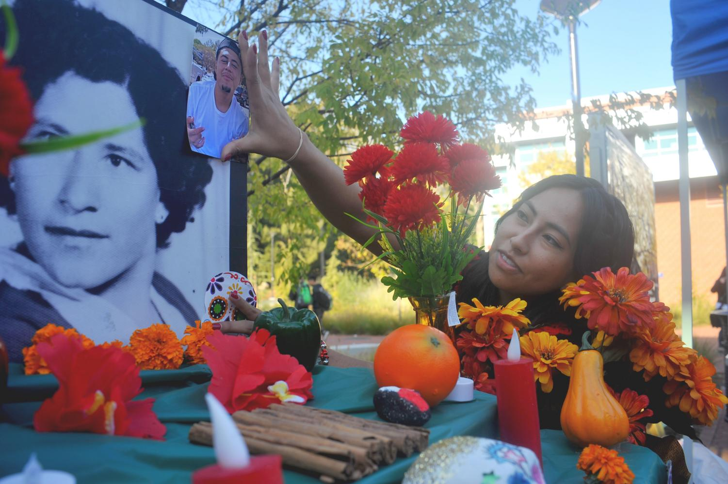La Raza Student Union members set up an altar where they placed decorations, food and pictures of deceased loved ones during the Dia De Lost Muertos event on Thursday.