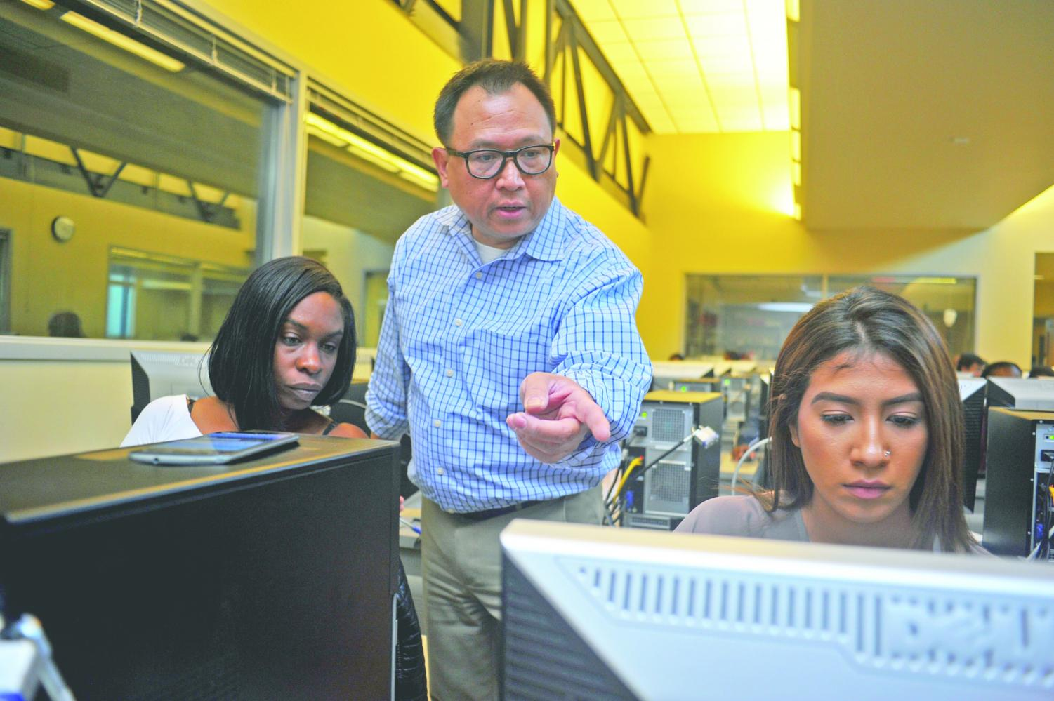 Computer science professor Francis Reyes (middle) guides nursing major Latonya Thomas (left) and undecided major Crystal Morales (right) through a computer science lecture in CTC-115 on Nov. 6.